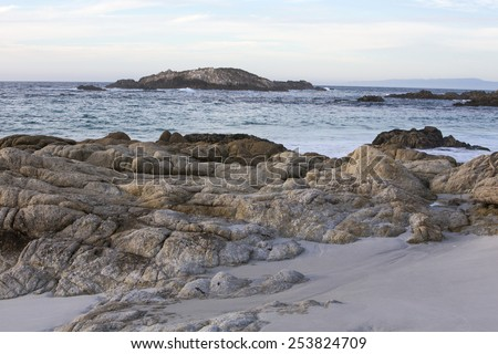 beautiful sand beach with rocks and blue waves - stock photo