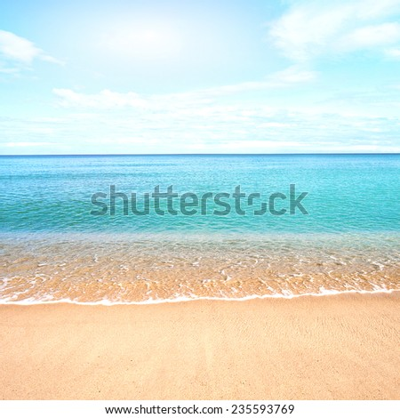 Beautiful sandy beach with calm water against blue skies. - stock photo