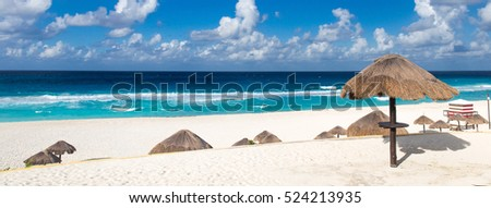 Beautiful sandy beach with thatch parasol