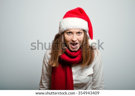 beautiful santa girl angry screams. Christmas hat isolated portrait of a woman on a gray background, studio photo.