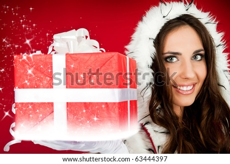 beautiful Santa helper holding sparkly Christmas present - stock photo