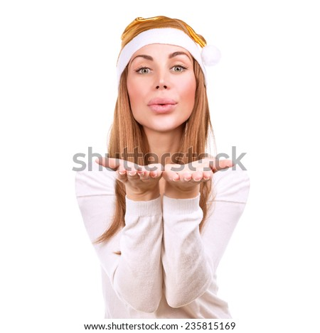 Beautiful Santa helper, portrait of attractive woman wearing festive golden hat sends an air kiss isolated on white background, happy Christmas holidays  - stock photo