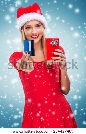 Beautiful santa woman holding gift box and credit card,snowfall background - stock photo