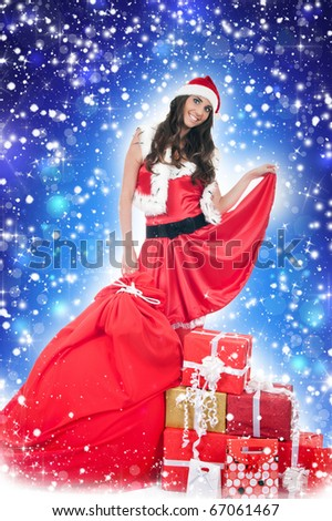 beautiful santa woman with presents on blue background - stock photo