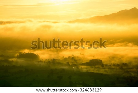 beautiful scenary in the north part of Thailand over the valley of mountain at sun rising giving a beautiful color on the mist in the field (selective focus, white balance shift and HDR effect apply) - stock photo