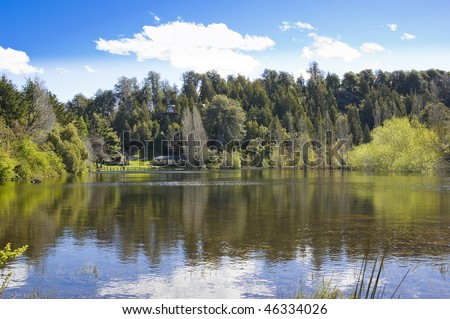 Beautiful scene of houses by the lake shore surrounded by forests. In Bariloche, Patagonia, Argentina. - stock photo