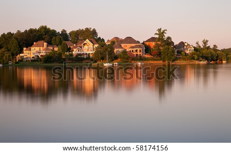 Beautiful scene of houses by the lake surrounded by forests  at sunset time - stock photo