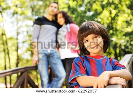 Beautiful scene of young happy family in natural park, three members: mother father behind and son in front looking at camera - stock photo