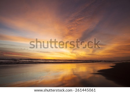 Beautiful scenery at sunset time on the tropical beach with orange color reflection of sky - stock photo