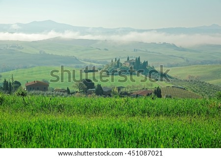 Beautiful scenery of a farm house on top of a rolling hill with green grassy fields & distant mountain silhouettes on horizon on a foggy spring morning in Pienza, San Quirico d'Orcia, Tuscany, Italy - stock photo