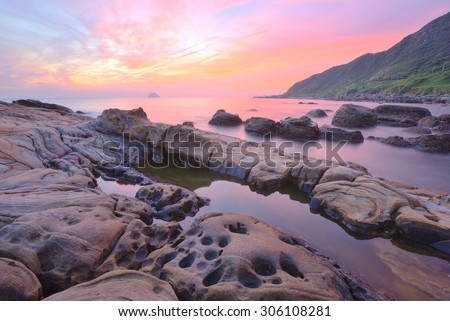 Beautiful scenery of dawning sky by rocky seashore in northern Taiwan (long exposure effect) With beautiful and tranquil reflection of water - stock photo
