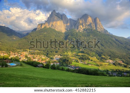 Beautiful scenery of Dolomiti mountains at sunset with view of rugged Schlern (Sciliar) peaks in background, villages & green meadows in foreground in Seis am Schlern, Castelrotto, South Tyrol, Italy - stock photo