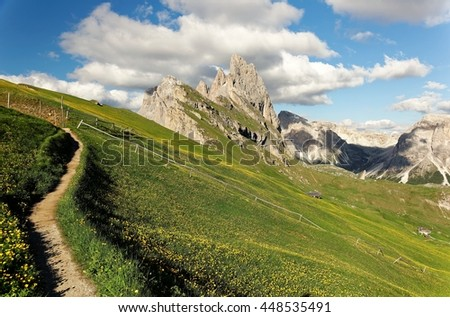 Beautiful scenery of Dolomiti on a sunny summer day with view of a trail on grassy hills & magnificent Odle (Geisler) mountain peaks in the background at Seceda, Val Gardena, South Tyrol, Italy Europe - stock photo