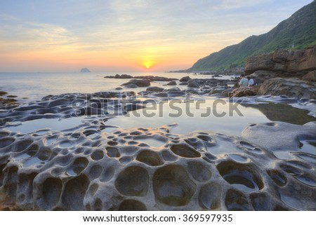 Beautiful scenery of golden rising sun reflecting on tranquil sea water by rocky seashore in northern Taiwan (long exposure effect)~  A happy couple enjoying fascinating view of sunrise sky at seaside - stock photo