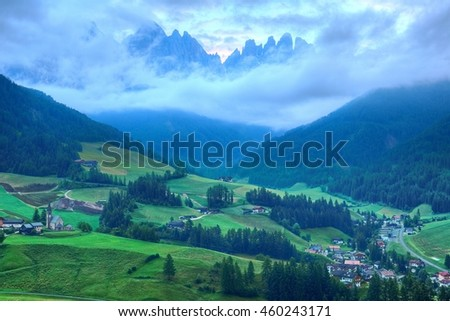 Beautiful scenery of majestic Puez Odle or Geisler Mountain Peaks in Val di Funes with view of Santa Maddalena (Magdalena) village in the green grassy valley in Dolomites, South Tyrol, Italy, Europe - stock photo