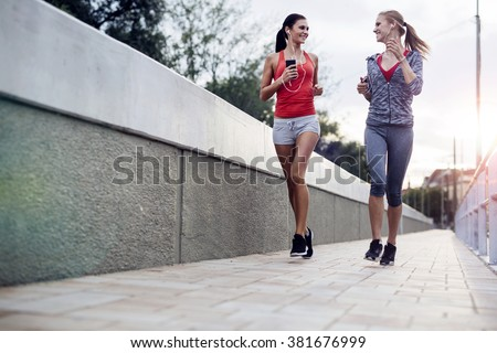 Beautiful scenery of two female joggers pursuing their activity outdoors in the city in dusk - stock photo