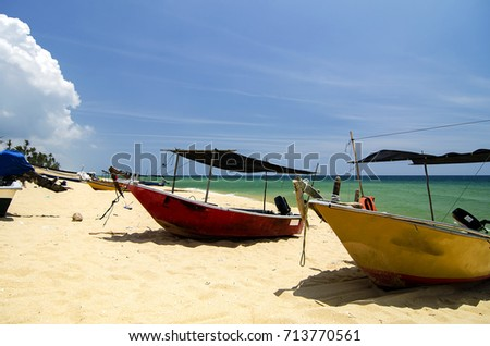 Beautiful scenery, traditional fisherman boat moored over beautiful sea view and sandy beach under bright sunny day