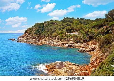 Beautiful scenery wild coast and beach bay of Spain, turquoise sea water, picturesque rocks against the blue sky with clouds - stock photo
