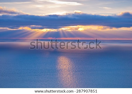 Beautiful scenery with clouds and sunbeams in blue and orange colors - stock photo