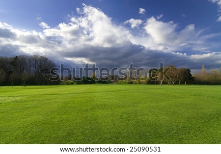 Beautiful scenery with green meadow and dramatic sky - stock photo