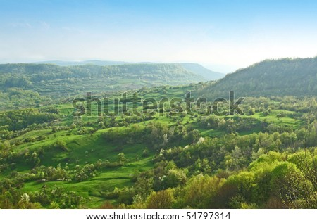 Beautiful scenery with low hills and valleys seen from above, with haze in the distance - stock photo