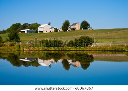 Beautiful scenic barn reflects in mirror like pond