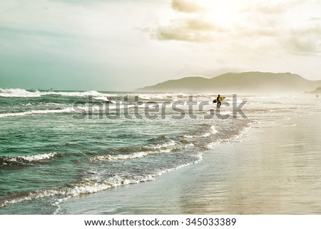 Beautiful scenic beach view at sunset with surfer siluette  on the ocean beach,  Florianopolis,  Brasil, South America - stock photo