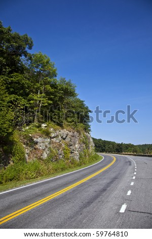 Beautiful scenic country road curves through Shenandoah  National Park. - stock photo