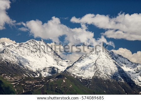 Beautiful scenic landscape of snow covered mountain peaks in Caucasus mountains at spring on a sunny day with blue sky and white clouds.
