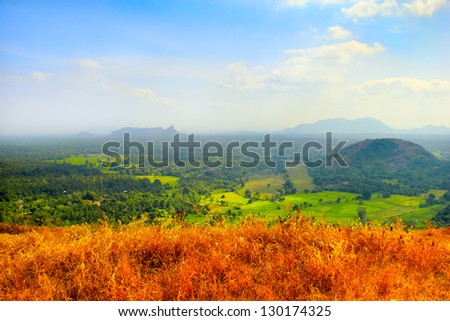 Beautiful scenic landscape of Sri Lanka with dry yellow grass, distant disappear in mist rocks, colorful green fields and wood, view from Yapahuwa Rock, South Asia - stock photo