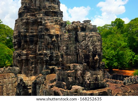 Beautiful scenic view - ancient Bayon temple (UNESCO world heritage site) decorated with stone faces - against the background of dramatic cloudy blue sky near Siem Reap, Cambodia, South East Asia  - stock photo