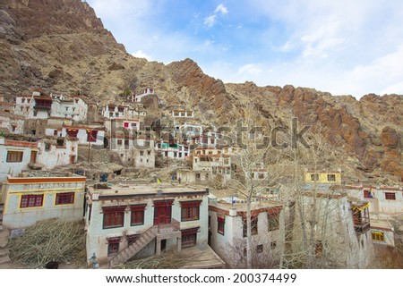 Beautiful scenic view - ancient Stongde Buddhist Monastery (Gompa) and traditional Tibet village against the background of barren mountain wall in Suru valley, Ladakh, Himalaya, Jammu & Kashmir, India - stock photo