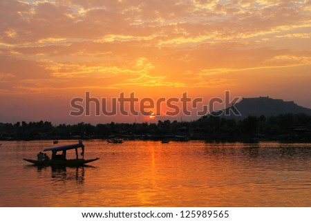 Beautiful scenic view - colorful sunset above calm water of Dal Lake with dramatic cloudy sky and traditional boat (shikara) shadow figures, Srinagar, Jammu & Kashmir, Northern India, Central Asia - stock photo