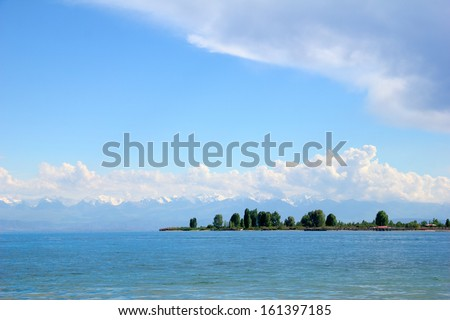 Beautiful scenic view - distant open wood amid the calm waters of Issyk-Kul Lake against the background of Tien Shan mountain range and cloudy blue sky, Kyrgyzstan, Central Asia - stock photo
