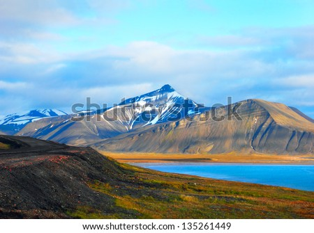 Beautiful scenic view of blue gulf under barren mountain range with melting snow against the background of dramatic evening sky near Barentsburg, Spitsbergen (Svalbard island), Norway, Greenland sea - stock photo