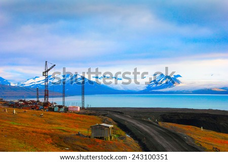Beautiful scenic view of blue gulf under barren mountains with melting snow, desert road and abandoned lift crane near Barentsburg, Spitsbergen (Svalbard island), Norway, Greenland sea - stock photo