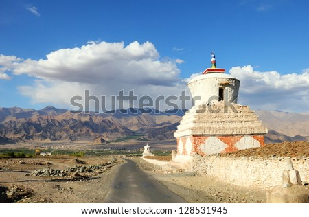 Beautiful scenic view of old white stupa near the road to Leh and distant colorful mountain range against the background of dramatic cloudy blue sky, Ladakh, Himalaya, Jammu & Kashmir, Northern India - stock photo