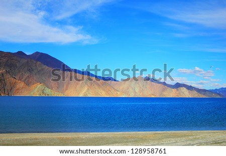 Beautiful scenic view of Pangong lake (Tso) against the background of distant colorful mountain and cloudy blue sky, Ladakh range, Jammu & Kashmir, Northern India - stock photo