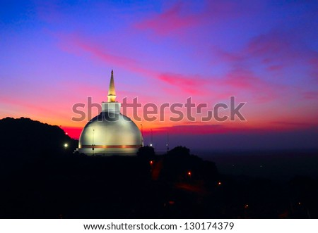 Beautiful scenic view of white Mahaseya Stupa against the background of colorful south land sunset with dramatic pink and blue cloudy sky, Mihintale - mountain peak near Anuradhapura, Sri Lanka island - stock photo