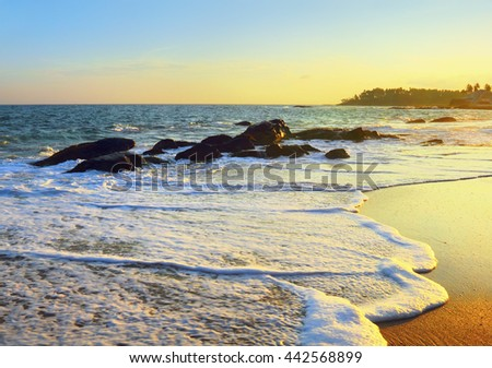Beautiful scenic view - wild beach with a waves splash, rocks, wet sand and sea foam against the background of colorful sunset sky in Tangalla (Tangalle), Sri Lanka island, Indian Ocean, South Asia  - stock photo