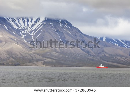 Beautiful scenic view with norge cruise boat docked at Longyearbyen port against the background of fogged black mountain and calm water of Advent Bay, Spitsbergen (Svalbard), Norway, Greenland sea