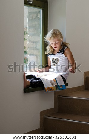 beautiful scholar blond girl sitting by the window and reading book - stock photo