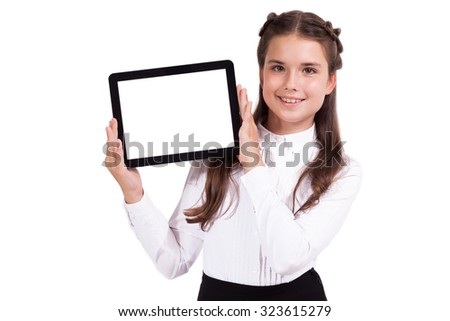 Beautiful school girl in a business suit holds a horizontal tablet in his hands and looking into the camera, Selective focus on the tablet - stock photo