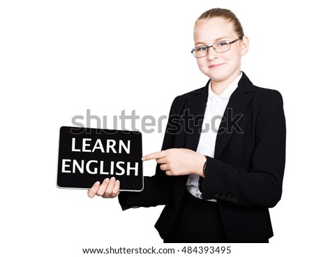 Beautiful school girl in a business suit holds a pc tablet in his hands and looking into the camera, on a pc tablet inscription learn English