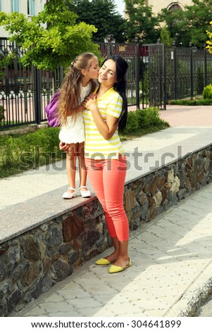 Beautiful school girl with mother walking outdoors - stock photo