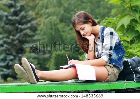 Beautiful school or college girl sitting on the bench with book and bag studing in a park  - stock photo