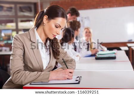 beautiful school teacher preparing lesson in classroom - stock photo