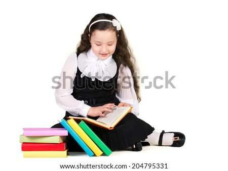 beautiful schoolgirl in black and white uniform sitting and reading book, near - stack of colorful books isolated on white - stock photo