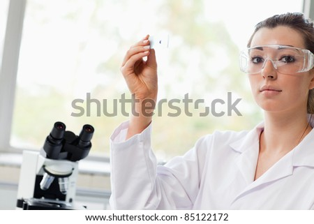 Beautiful science student holding a microscope slide in a laboratory - stock photo