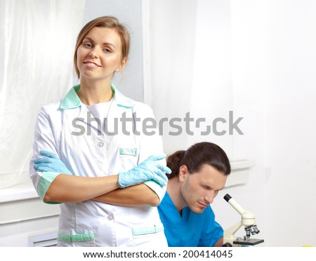 beautiful scientist in the laboratory on a background of a colleague which looks through a microscope in a lab - stock photo